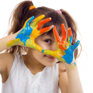 Young girl playing with blue, orange, and yellow paint with hands.