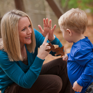 Woman signing the word 'Leaf' in American Sign Language while communicating with her son